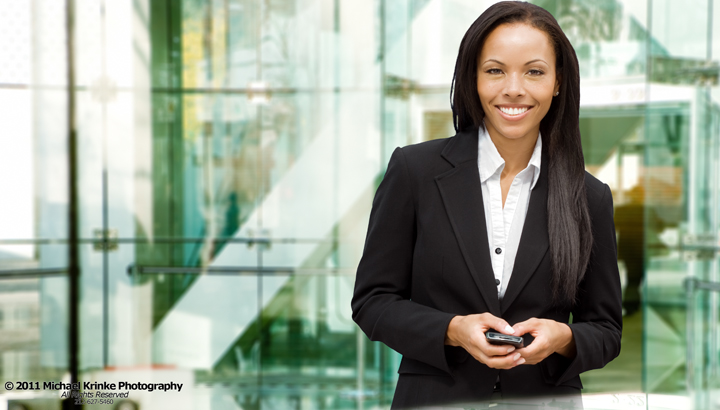 Young happy African American business woman with smart phone